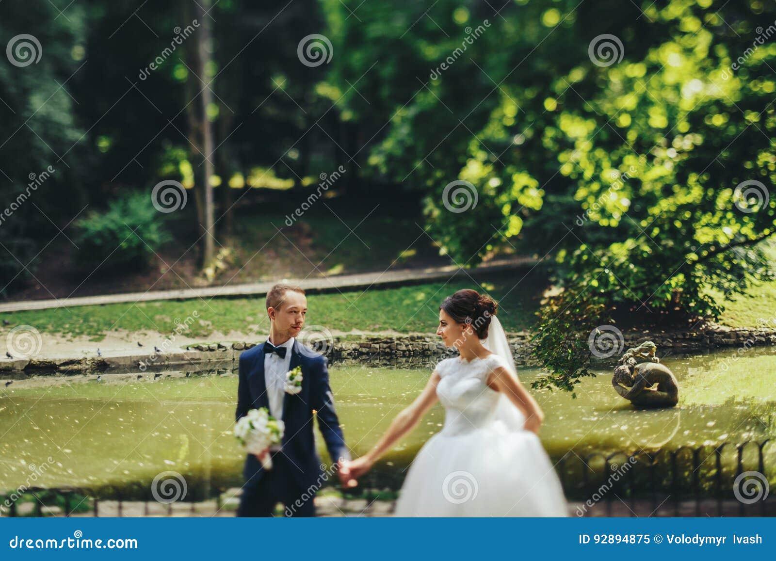 Bräutigam betrachtet eine Braut, die mit ihr entlang dem Seeufer geht