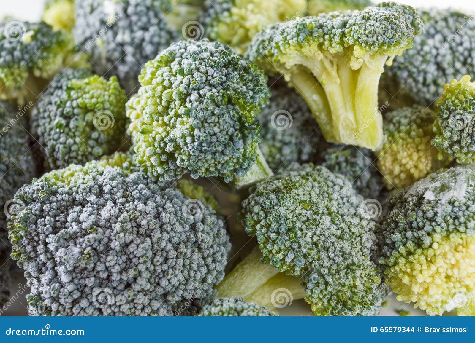 Brócolis congelados com os cristais de gelo no fundo branco