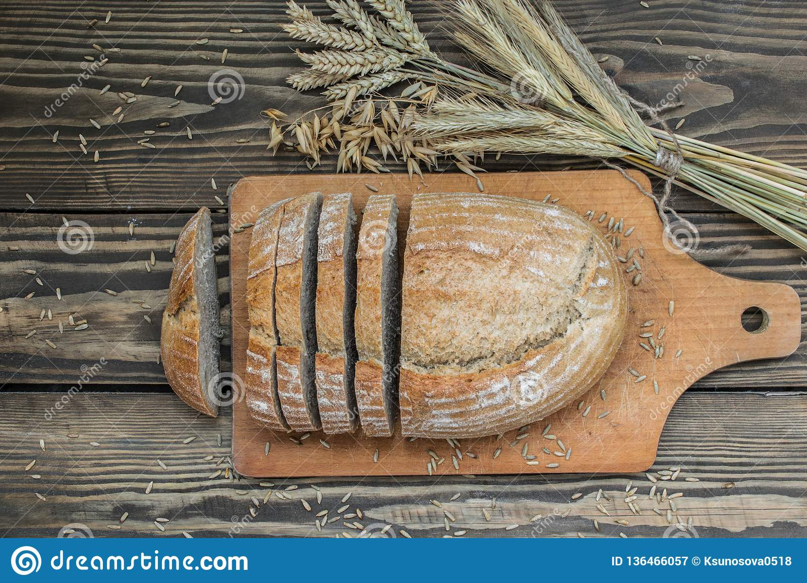 Bröd av en blandning av mjöl som skivas på en träbakgrund