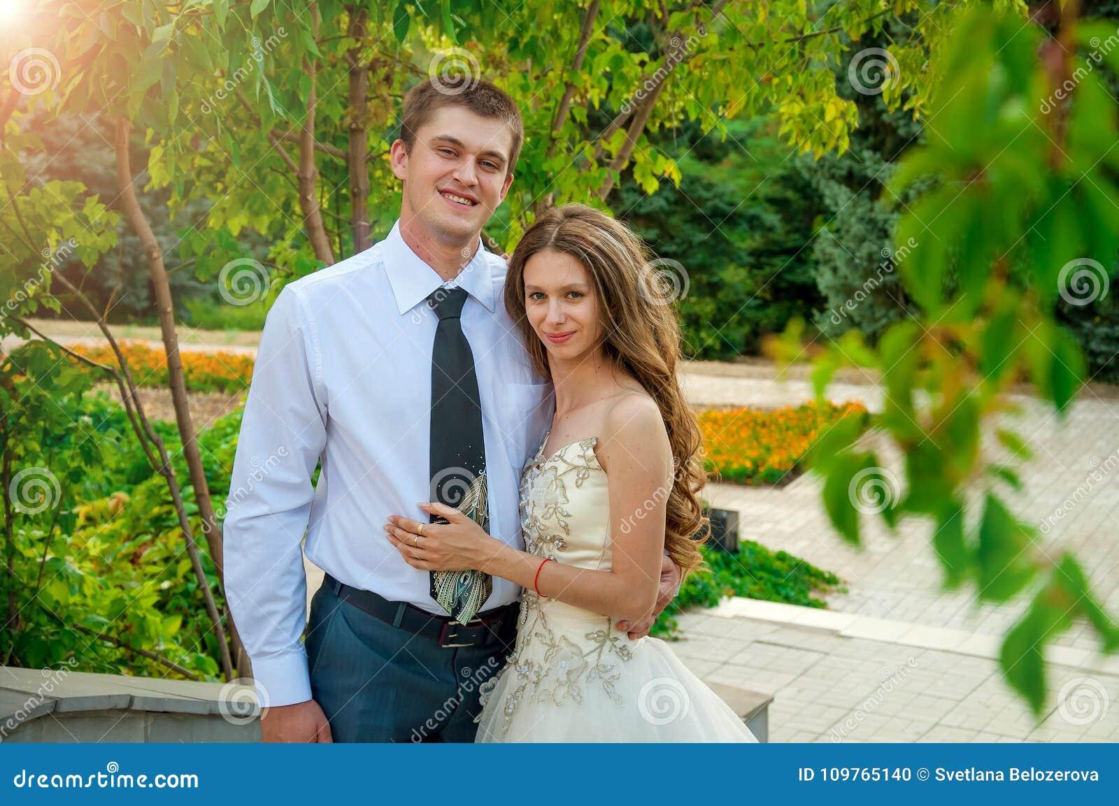 Bröllop för tappning för klädpardag lyckligt Lyckliga par in i parkera Det lyckliga ung flickainnehav hänger lös på en vitbakgrun