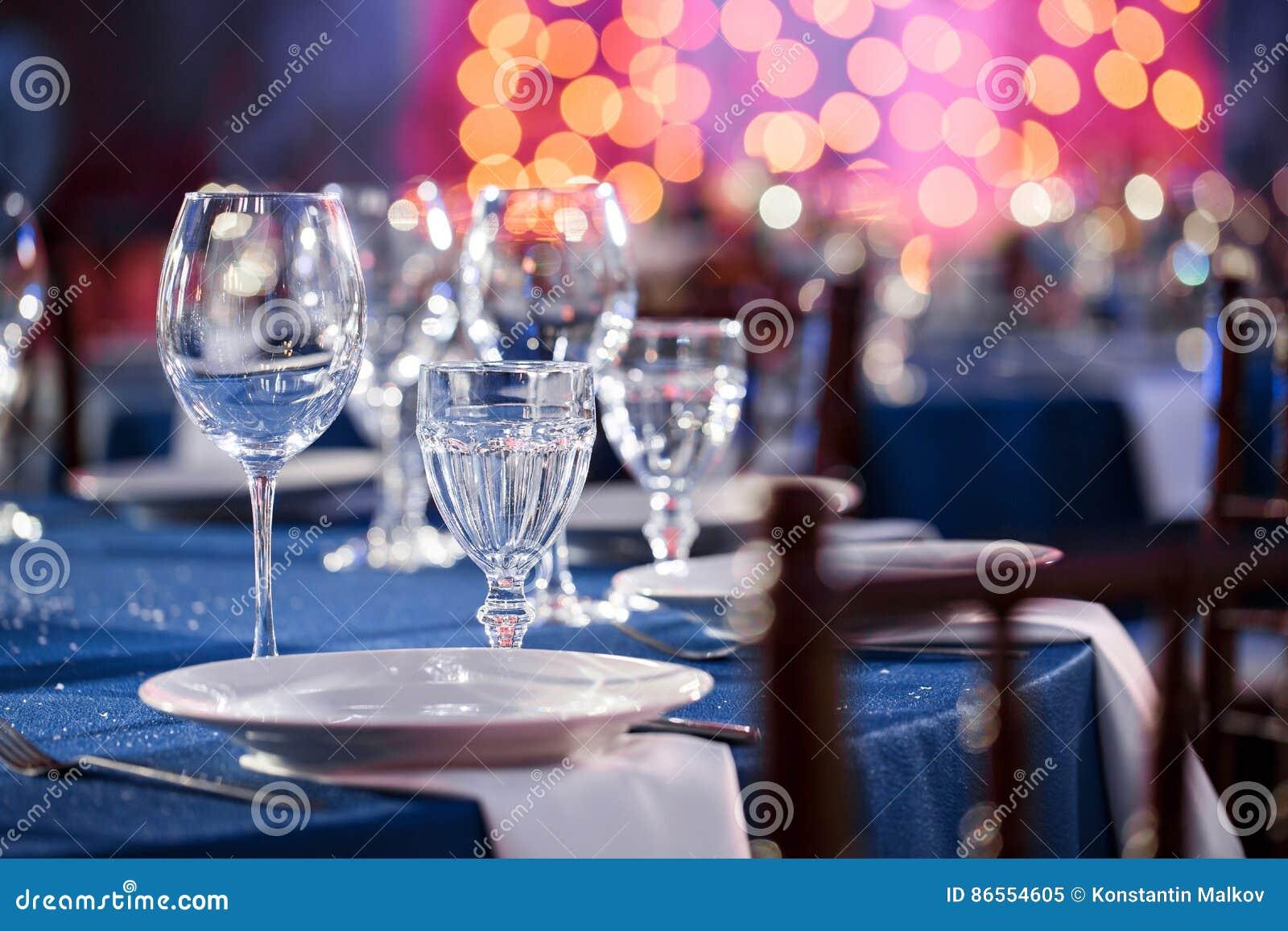 Bröllop _ Stolarna och den runda tabellen för gäster som tjänas som med bestick och lerkärl och täckas med en blått