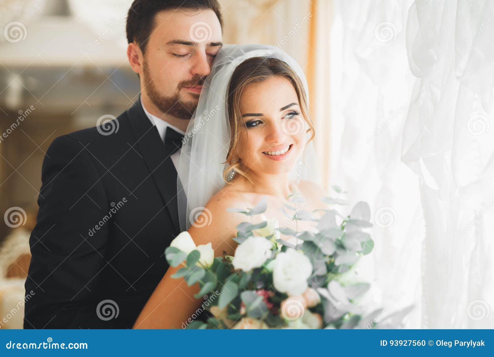 Bröllopfotoforsen av nygifta personerna kopplar ihop att posera i ett härligt hotell