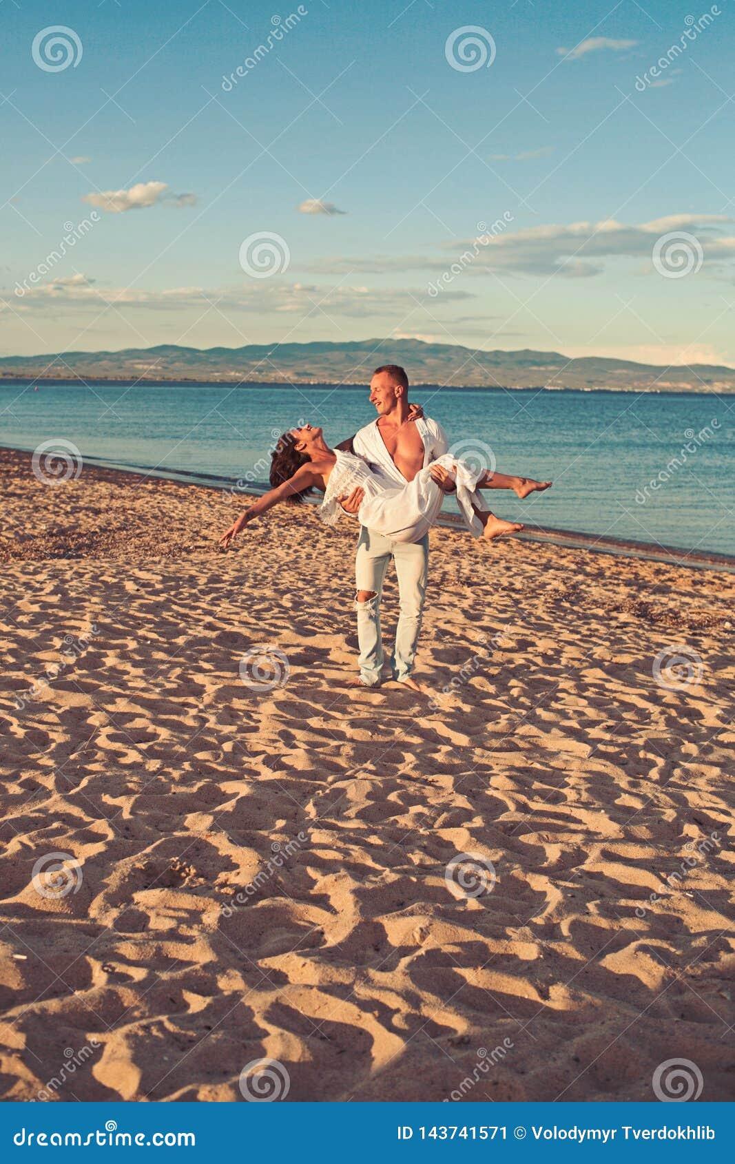 Bröllopsresabegrepp bröllopsresa av unga härliga par med maninnehavkvinnan på händer på den sandiga stranden