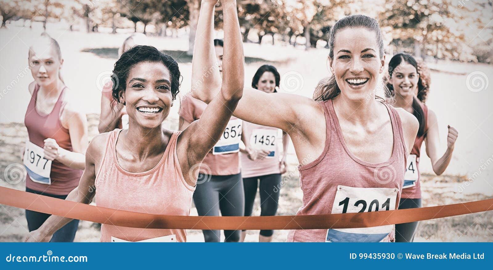 Bröstcancerdeltagare som korsar mållinjen på loppet