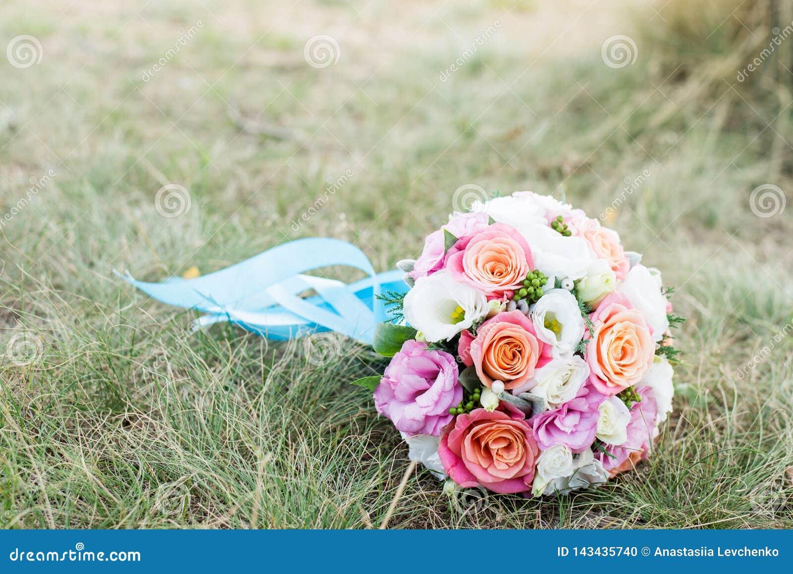 Br?llop f?r reng?ringsduk f?r mall f?r sida f?r bakgrundskorth?lsning universal Brudens bukett med rosa och vita blommor på gräse
