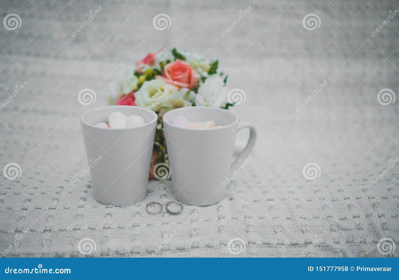 Br?llopfotografi gifta sig övervintrar detaljer bröllop två vita koppar med och marshmallower, en brud- bukett och cirklar