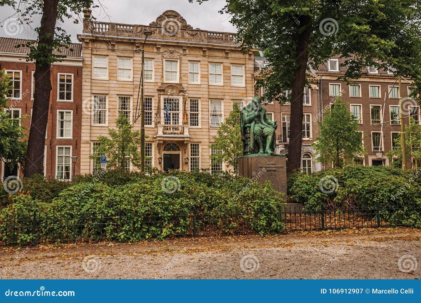 Brązowa statua, ogród z obfitolistnymi drzewami przed ceglanymi domami i chmurny niebo w Haga,