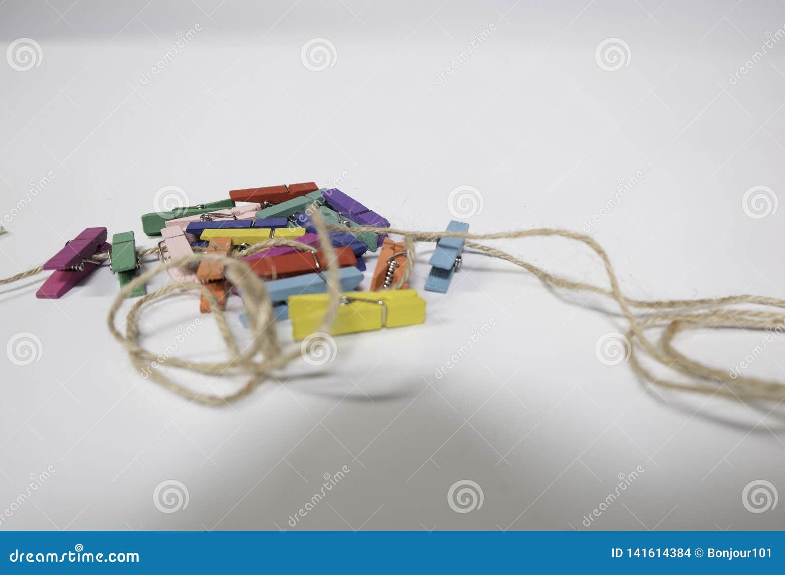 Braçadeiras pequenas Multi-coloridas de pano, empilhando junto em uma pilha e em uma corda O fundo é branco
