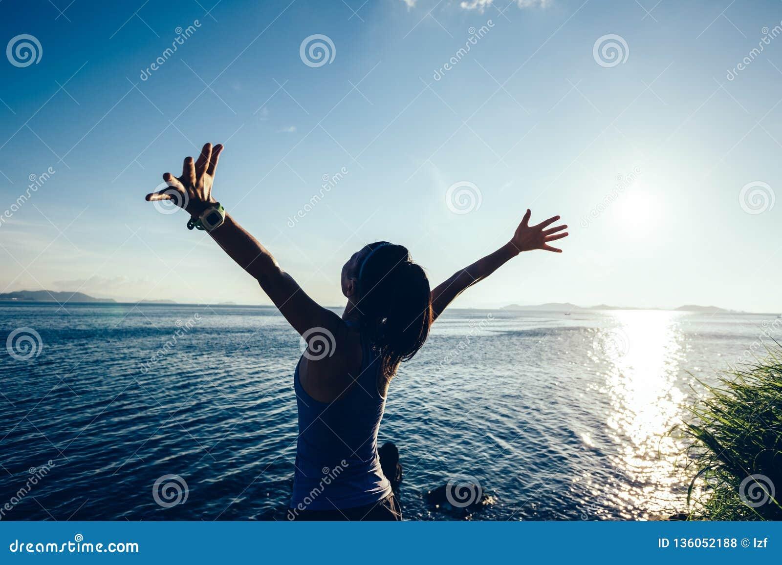 Braços abertos do basculador da mulher no beira-mar do nascer do sol