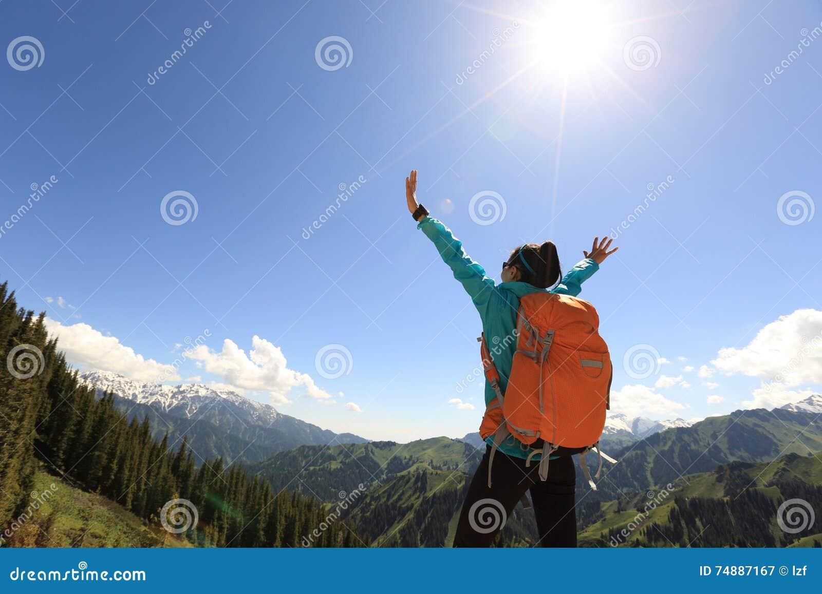 Braços abertos do mochileiro bem sucedido da mulher no pico de montanha