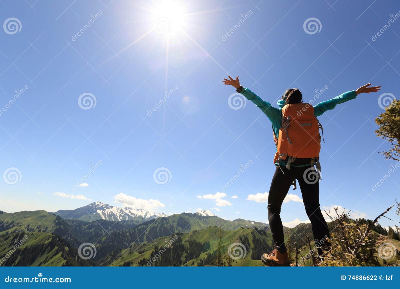 Braços abertos do mochileiro da mulher no pico de montanha