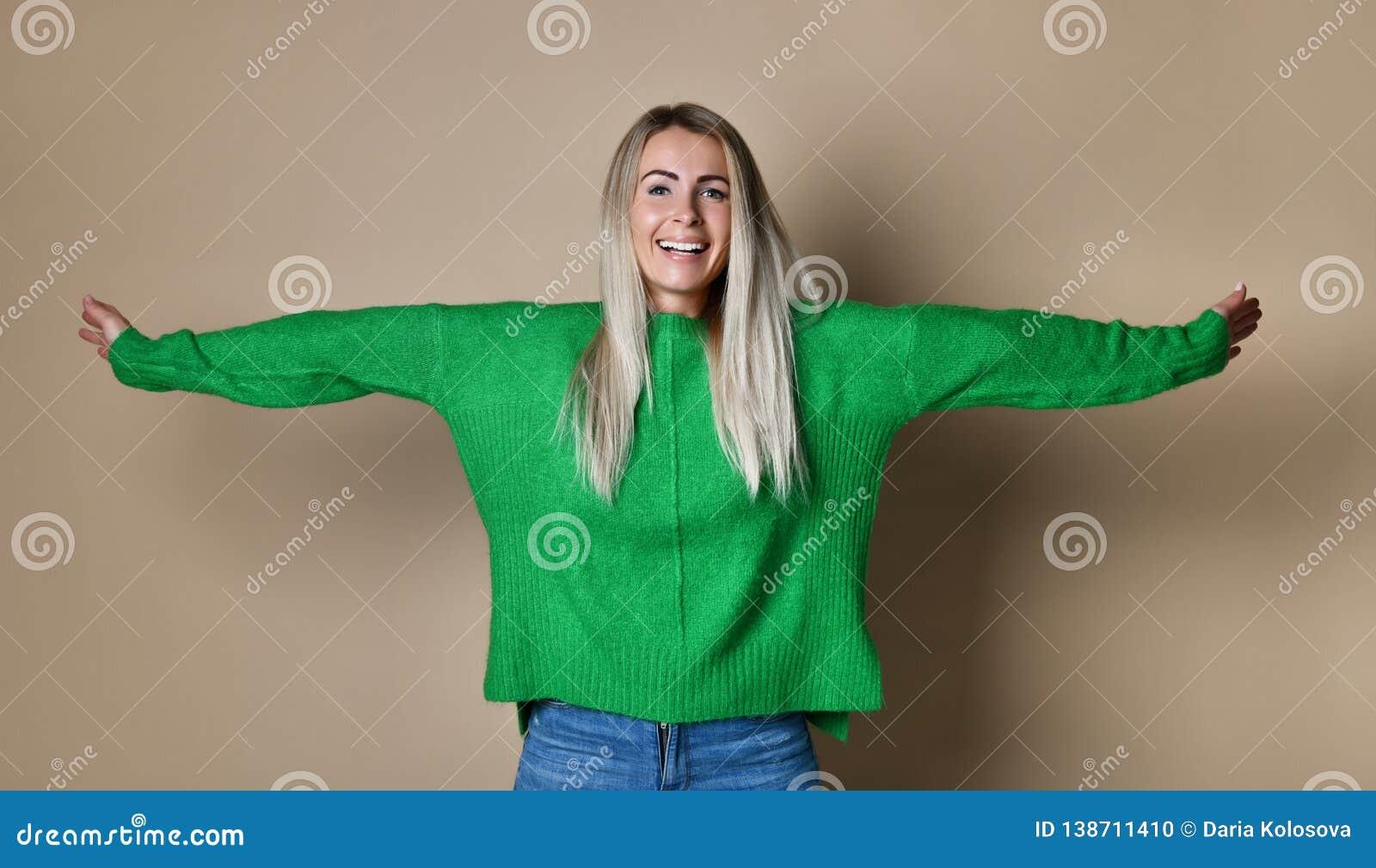 Braços da jovem mulher estendidos pela parede do estúdio que aprecia a liberdade e a vida