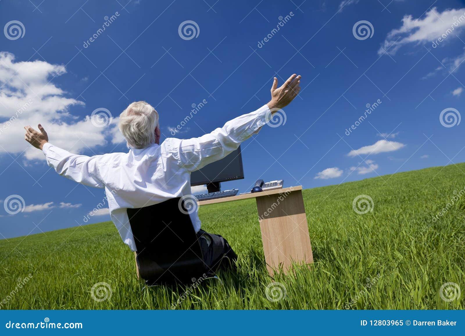 Braços do homem de negócios levantados na mesa no campo verde