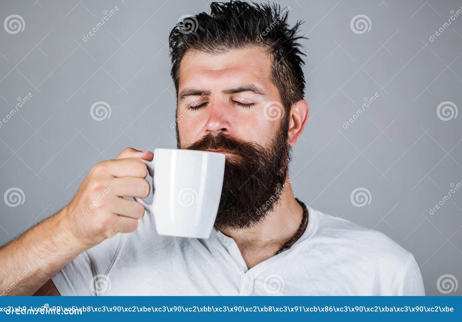 Bra morgon man som rymmer ett koppte Ta tid på som den kaffekoppen, tidningen och penna Den stiliga skäggiga mannen rymmer koppen