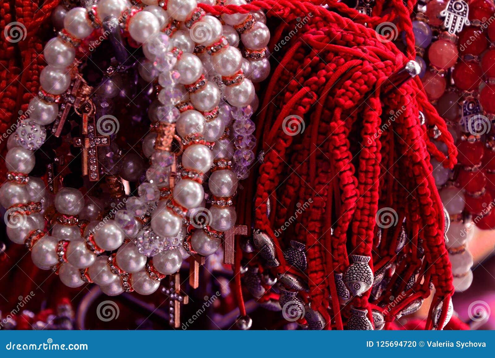 Braccialetto intrecciato dal filo e dalle perle rossi amuleto contro il malocchio sul polso da Gerusalemme, Israele