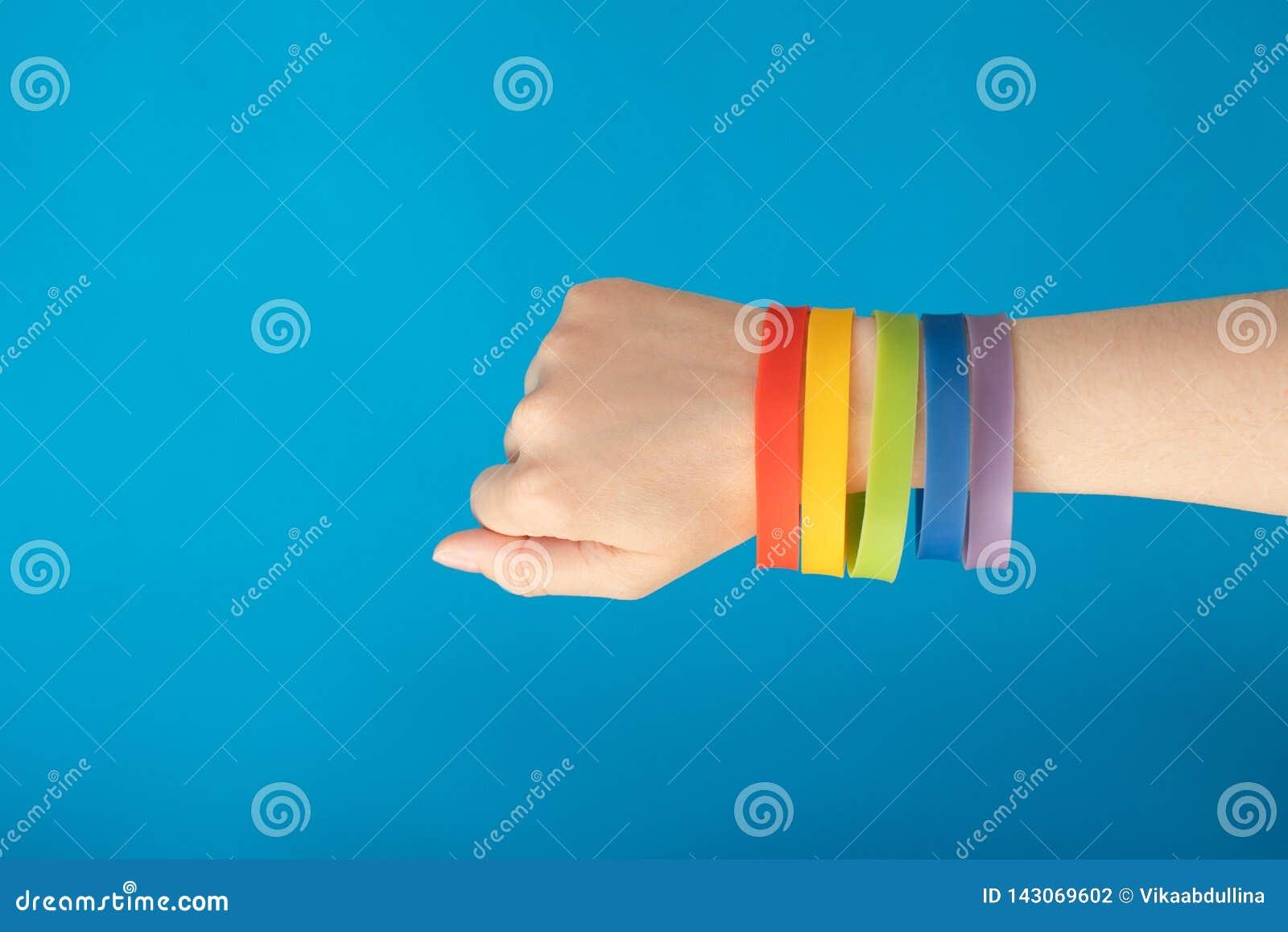Bracelet de bracelet du drapeau LGBT d arc-en-ciel sur la main femelle sur le fond bleu