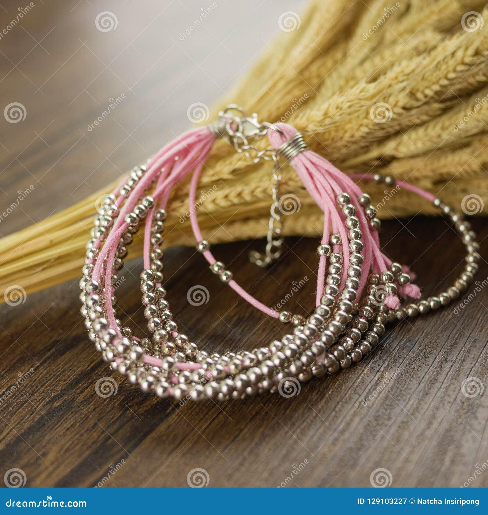 Bracelete cor-de-rosa no fundo de madeira