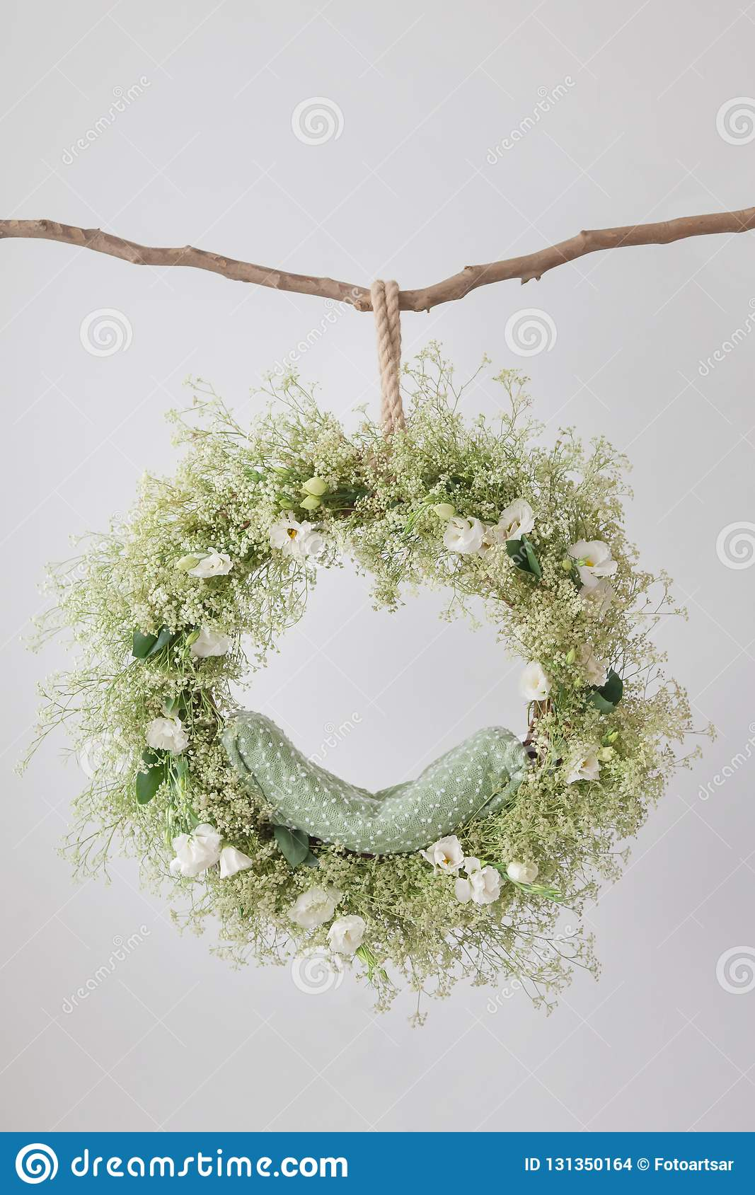 On the branch hangs a ring cradle for a photo shoot of newborns, a dream catcher, a floral arrangement with eustomas