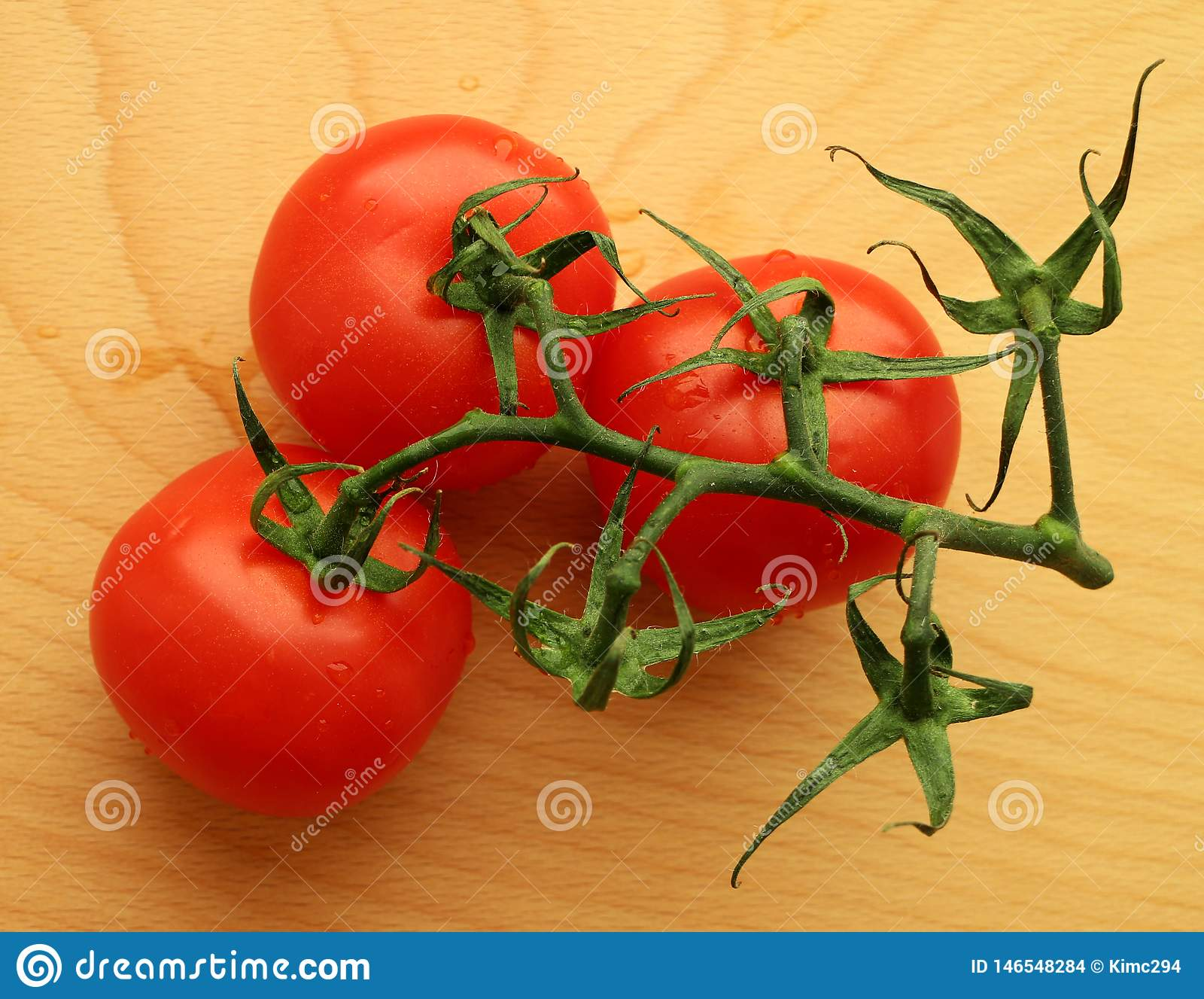 Three tomatoes on a twig on a wooden cutting board.