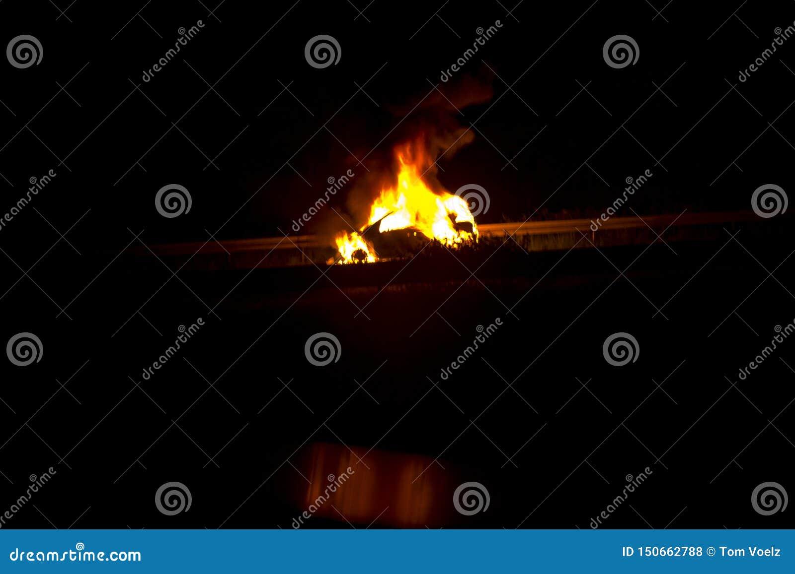 Brandende auto op de weg in de nacht
