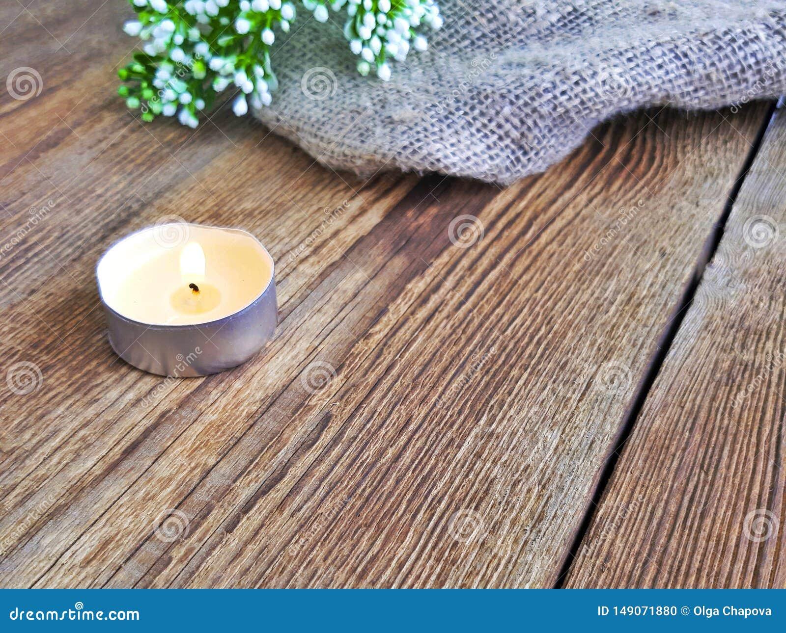 Brandende kaars op houten lijst Over zwarte