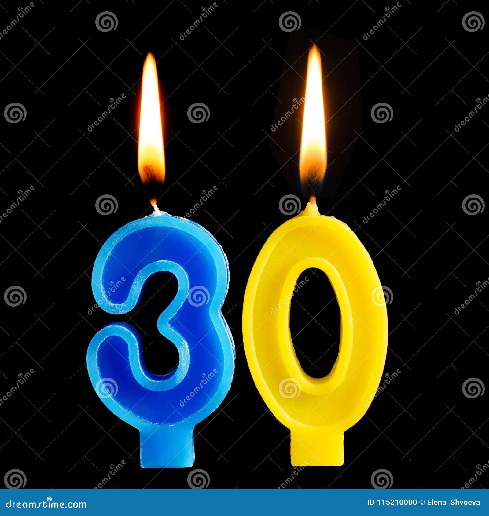 Brandende verjaardagskaarsen in de vorm van 30 dertig die cijfers voor cake op zwarte achtergrond worden geïsoleerd Het concept h