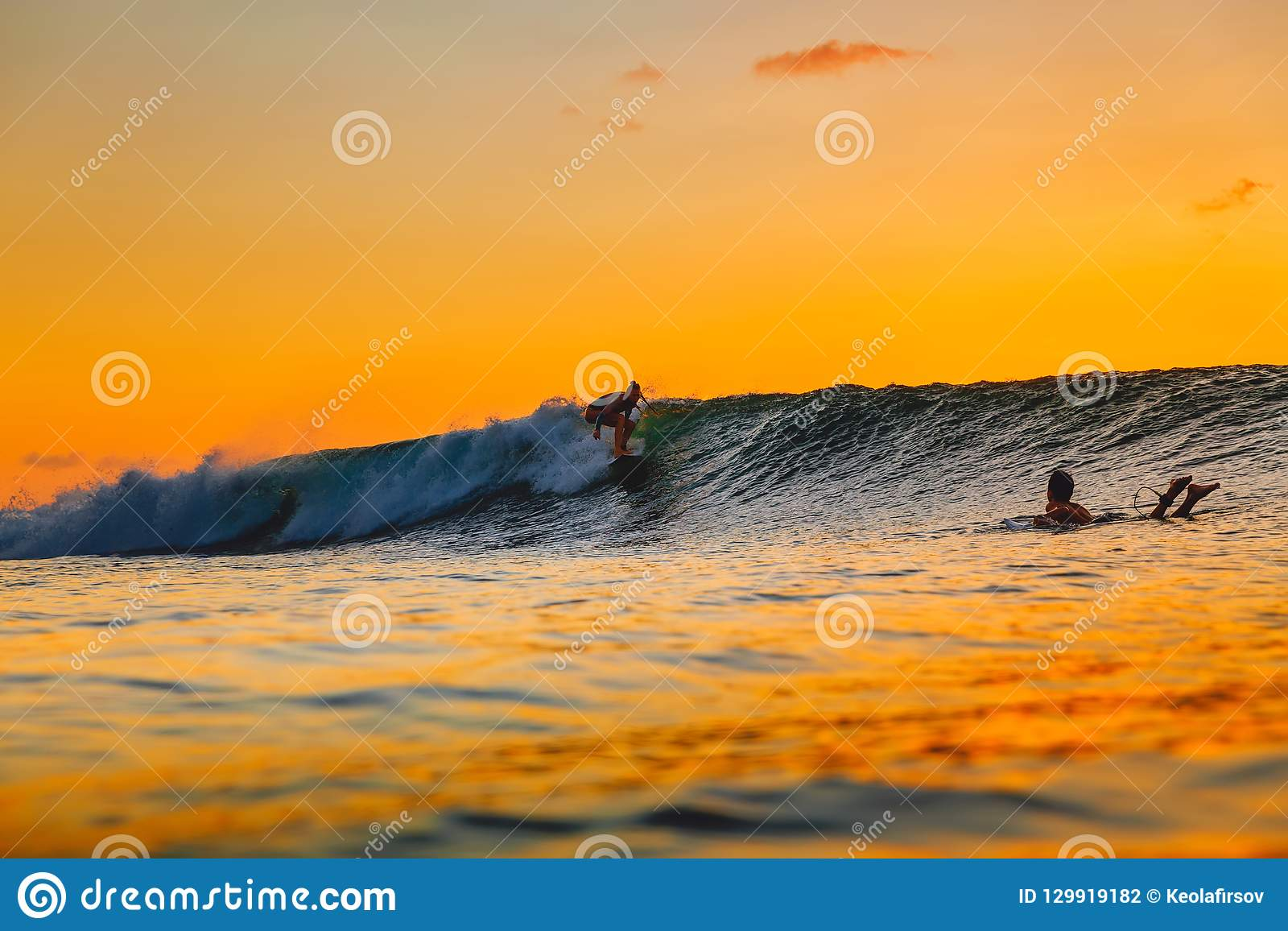 Brandingsmeisje op surfplank bij zonsondergang Vrouw in oceaan, zonsondergang het surfen