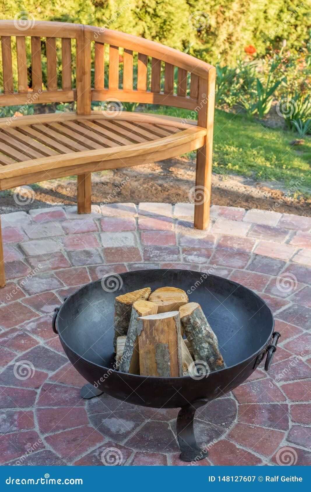 Brandkom in de tuin als comfortabele plaats van rust met houten bank op de achtergrond