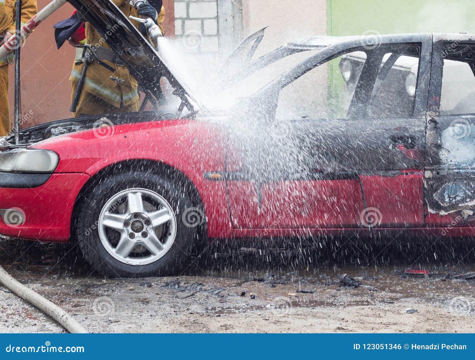 Brandmän släcker en brinnande bil med vatten, avfyrar, släcker