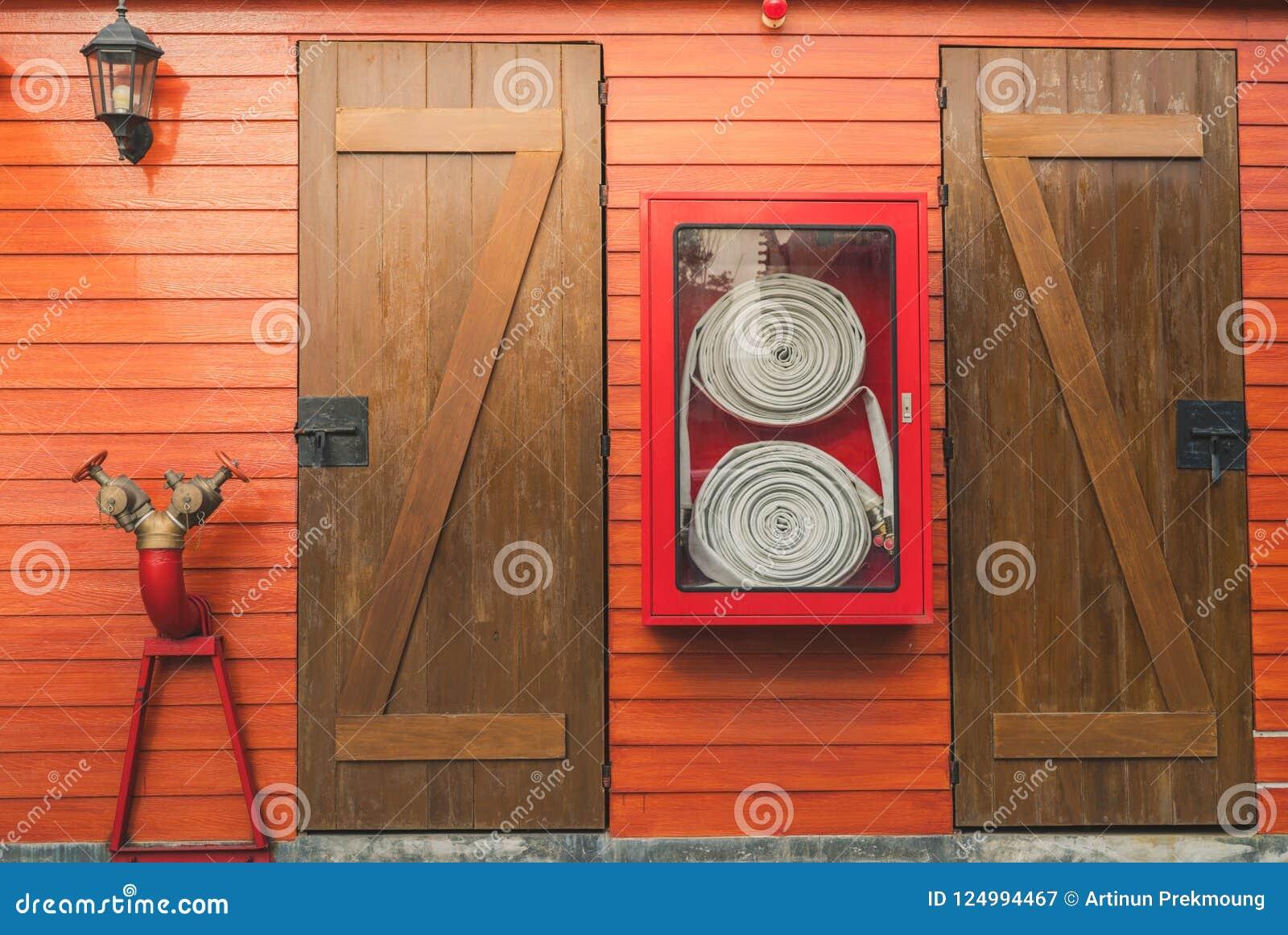 Brandslang i det röda kabinettet som hänger på den orange träväggen Ask för nöd- utrustning för brand för säkerhet och trygghetsy