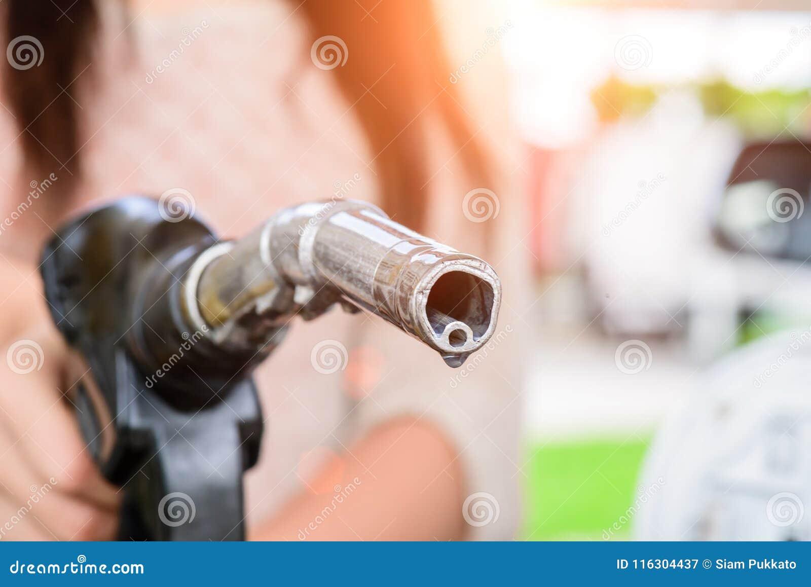 Brandstof van de vrouwen de pompende benzine in auto bij benzinestation
