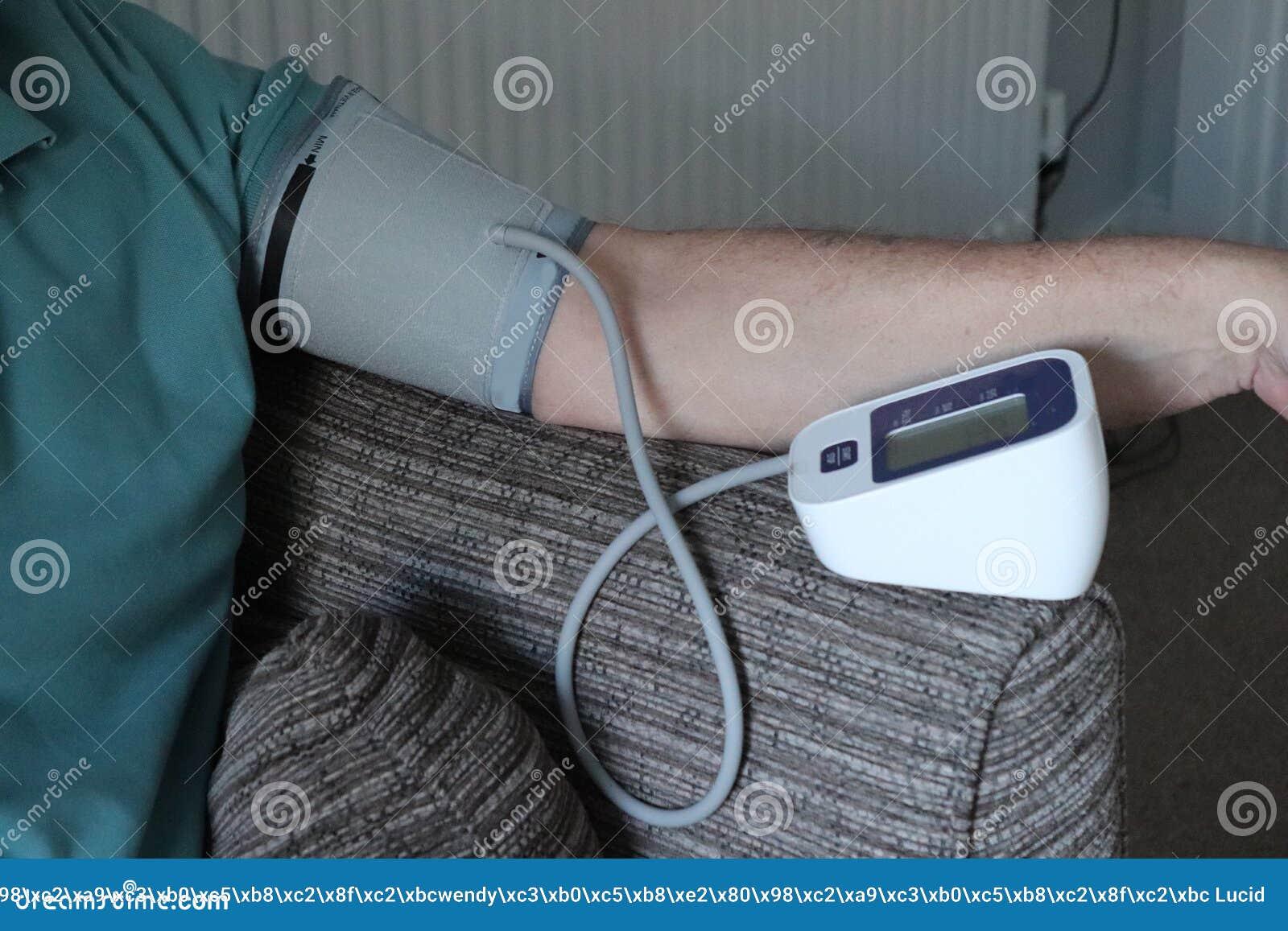 Bras et machine adultes de tension artérielle dans la maison lecture record pour des médecins