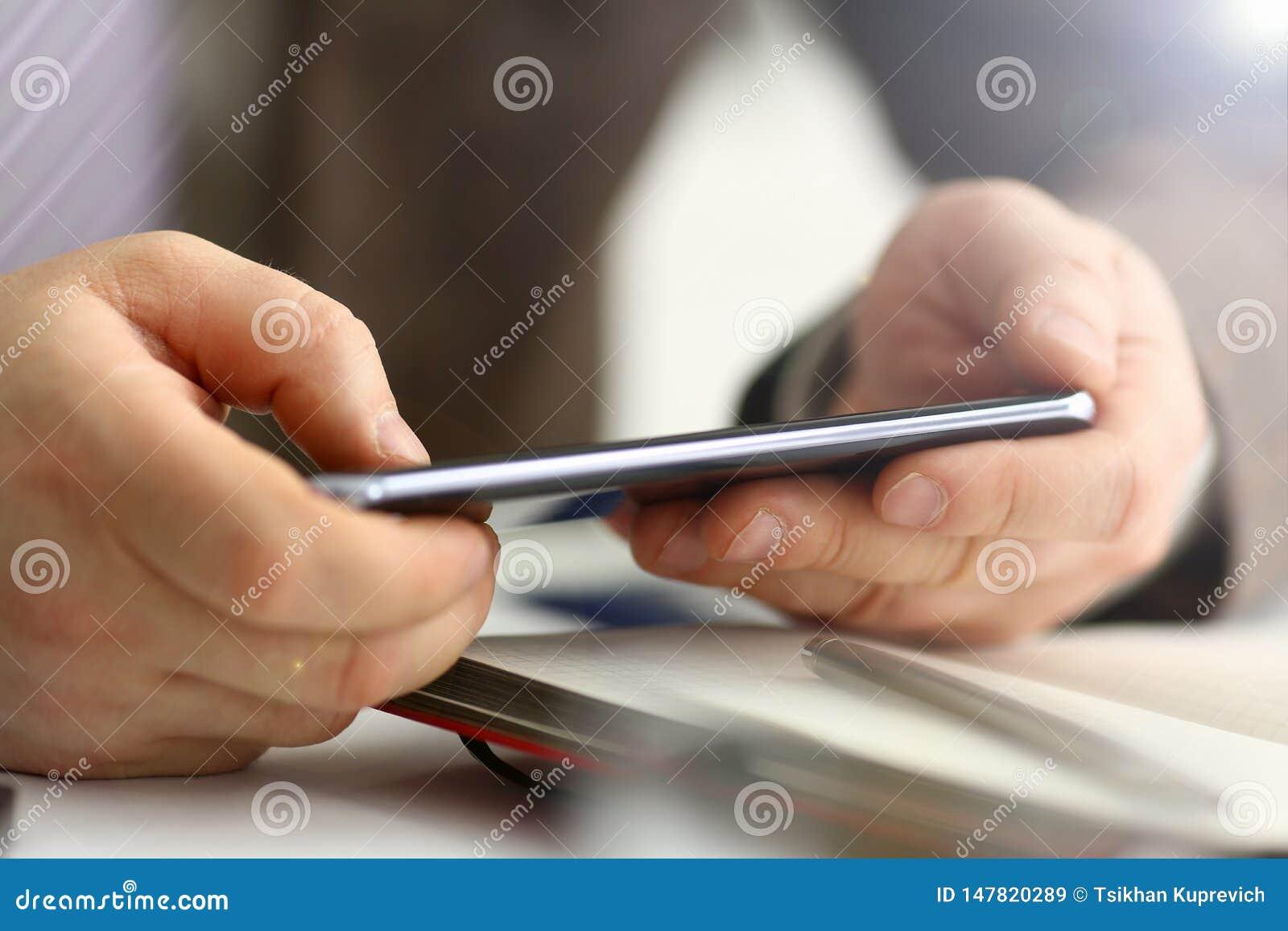 Bras masculin dans le stylo de t?l?phone et d argent de prise de costume
