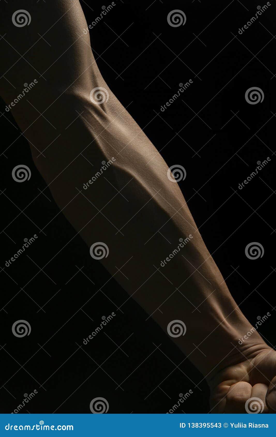 Bras masculin musculaire masculin avec les veines gonflées en gros plan sur un fond noir