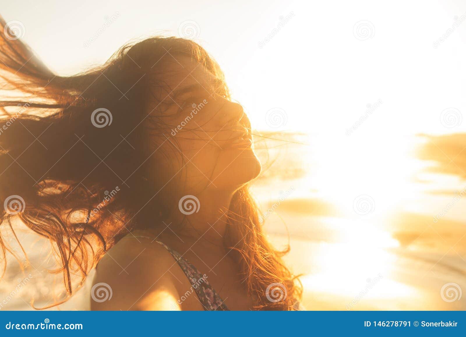 Bras ouverts heureux et gratuits de femme de libert? sur la plage au coucher du soleil ensoleill?