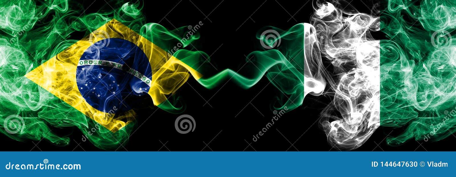 Brasilien gegen Nigeria, nigerische Rauchflaggen nebeneinander gesetzt Dicke farbige seidige Rauchflaggen des Brasilianers und de
