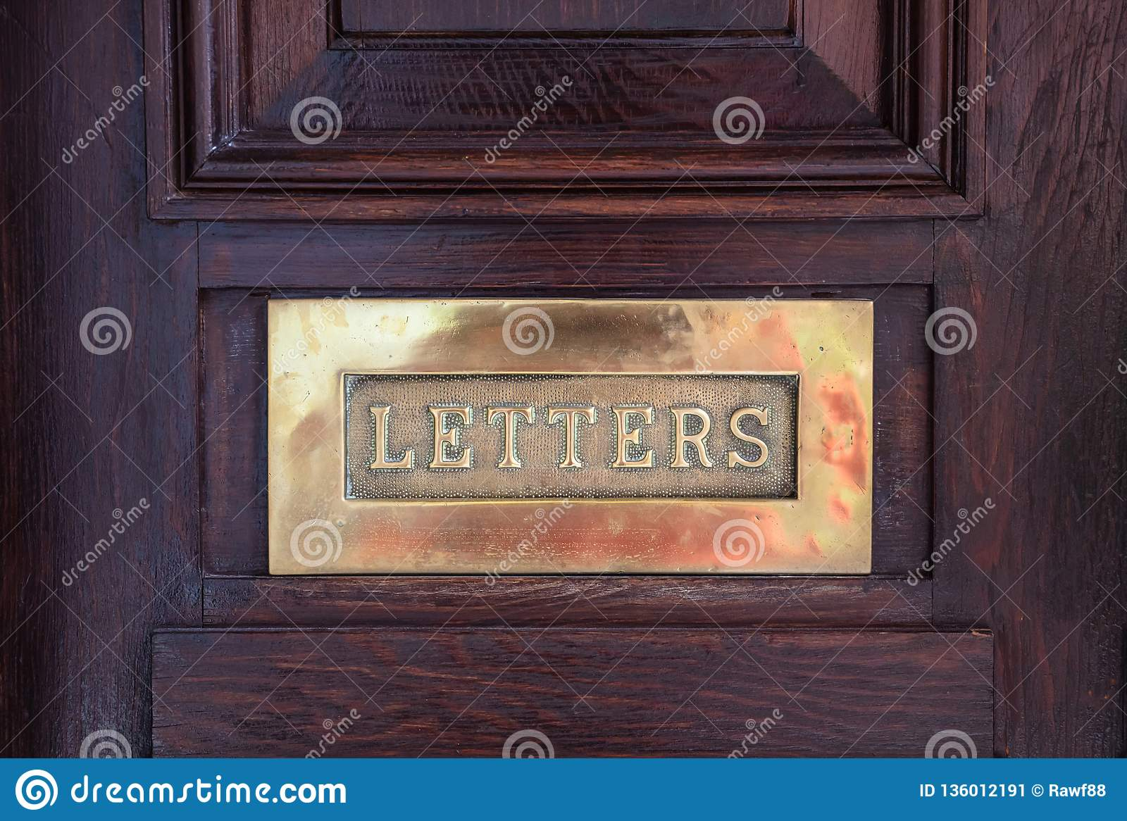 Brass mail letter box on a wooden front door, text letters
