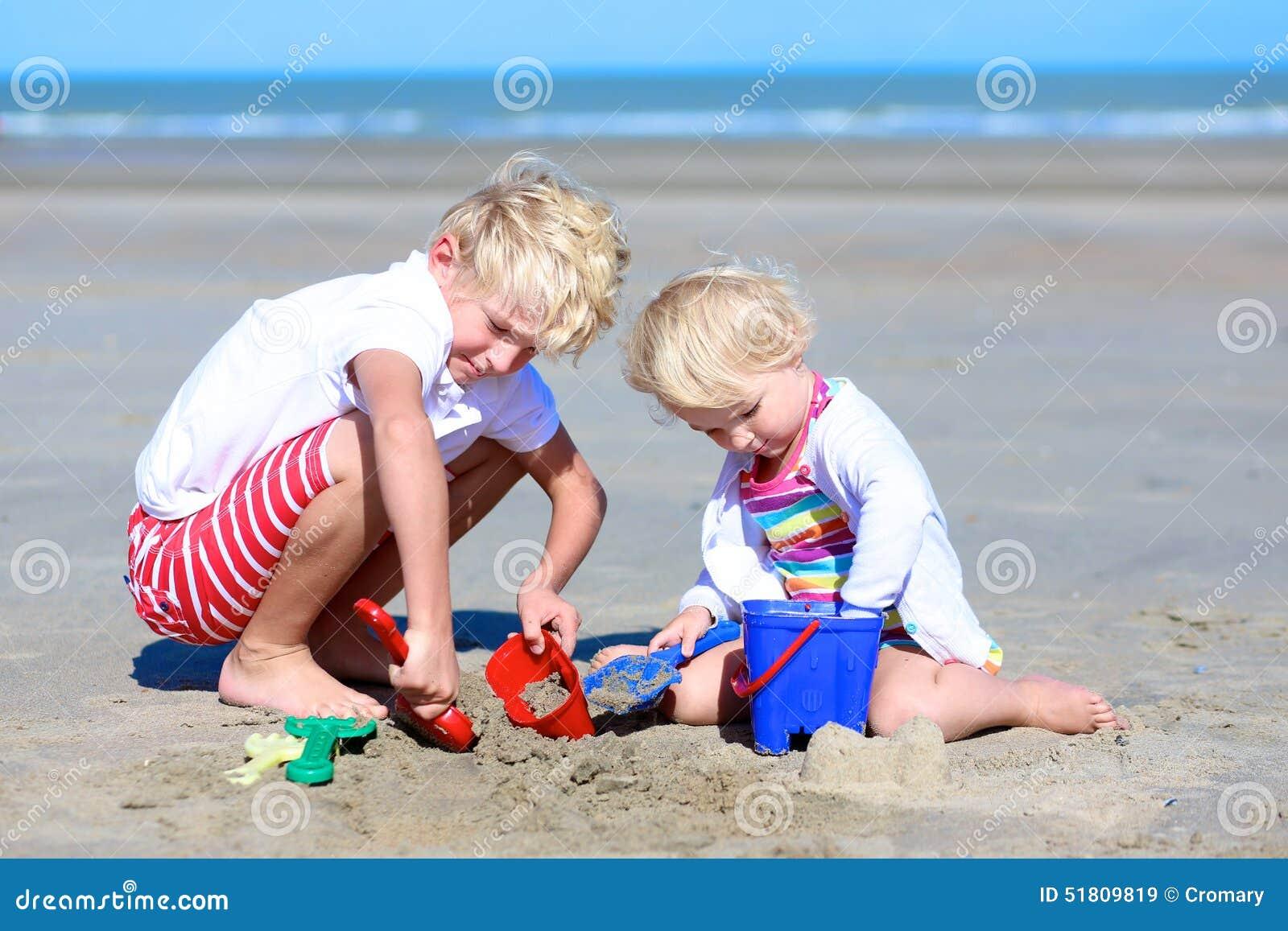 Brat i siostra bawić się z piaskiem na plaży