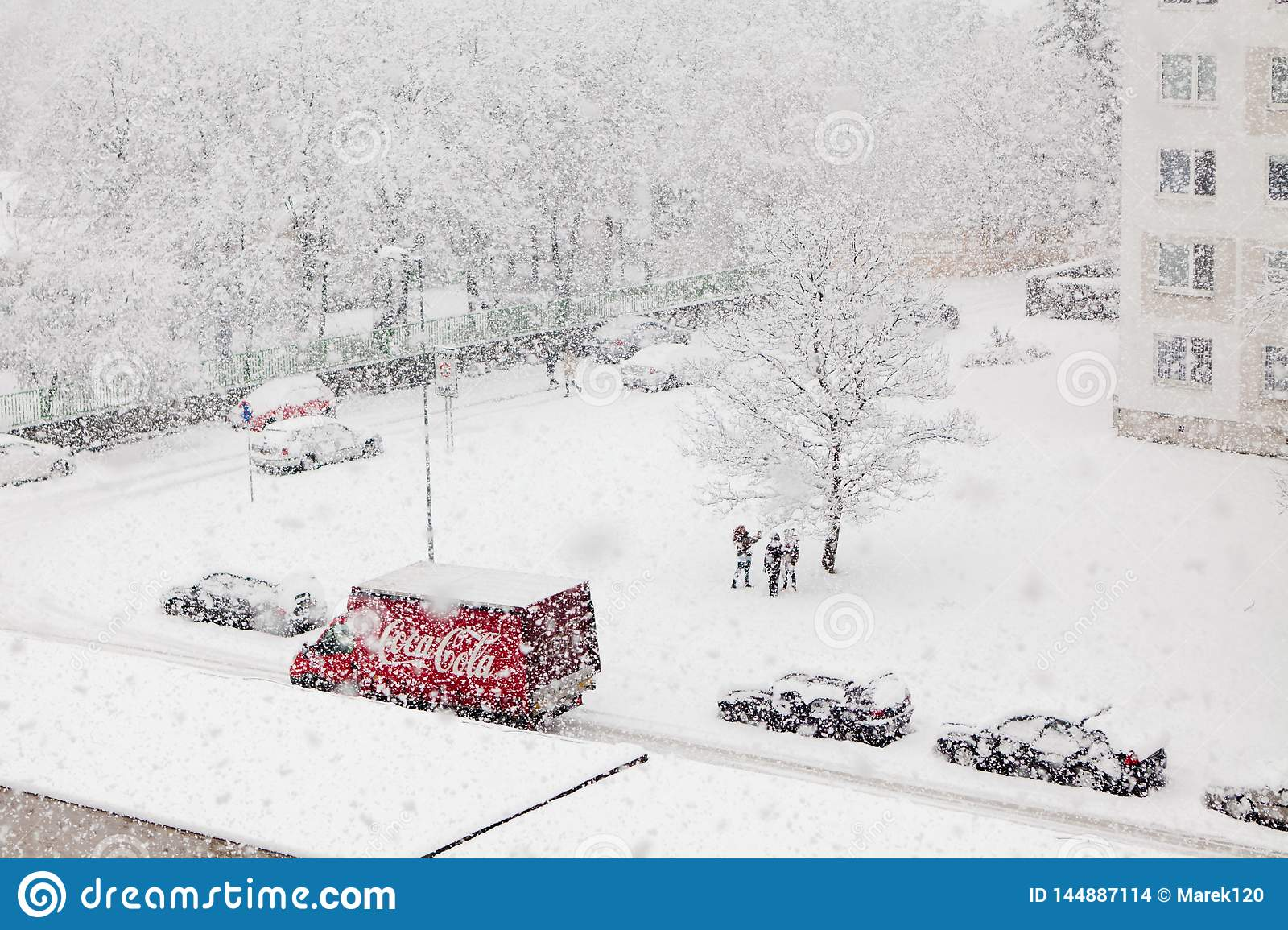 Bratislava, Slovakia, 30th. January, 2015 : Coca Cola red delivery car in heavy snowing - children enjoy snow