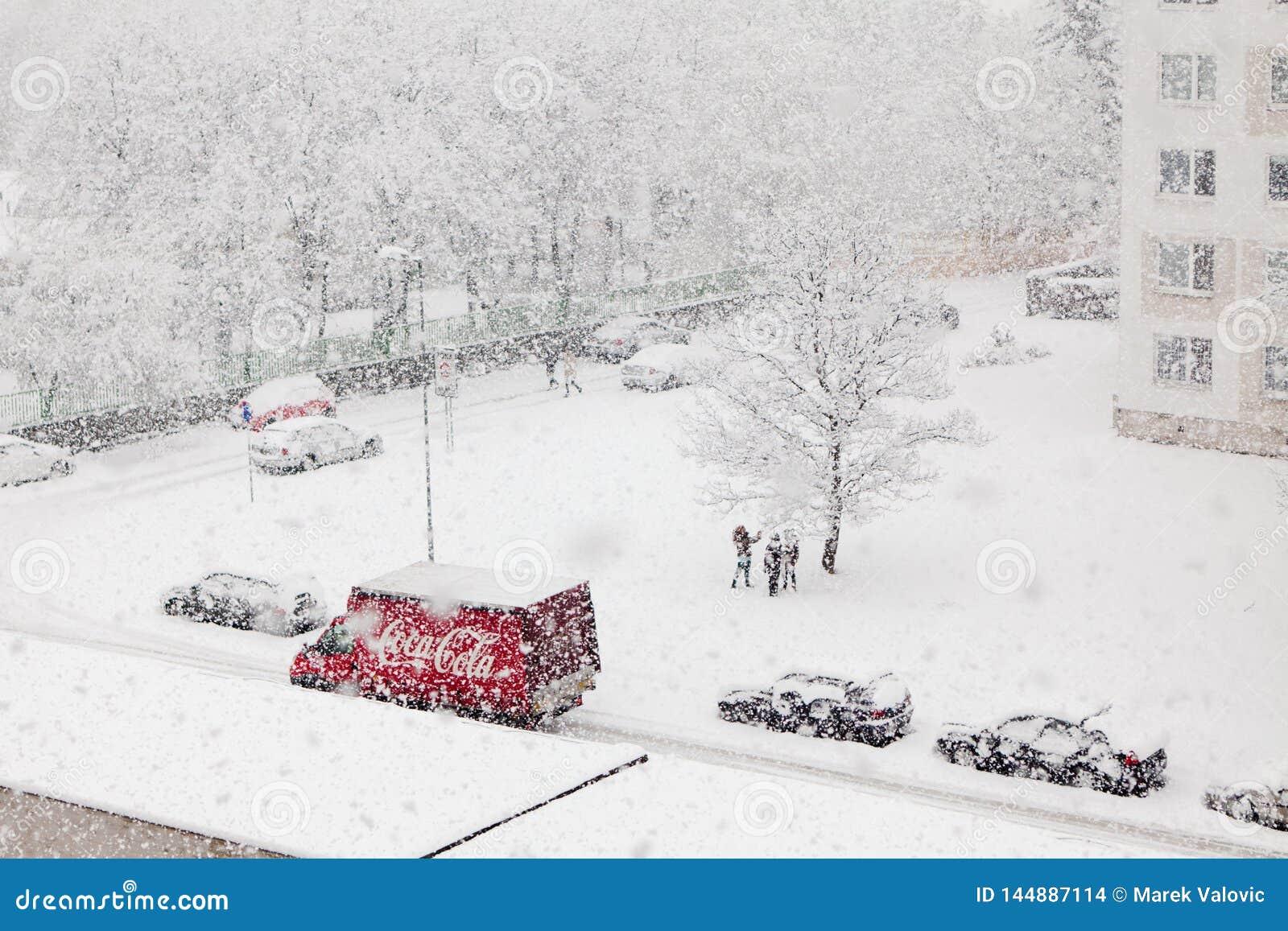 Bratislava, Slowakije, dertigste Januari, 2015: Auto van de coca-cola de rode levering in het zware sneeuwen - de kinderen geniet