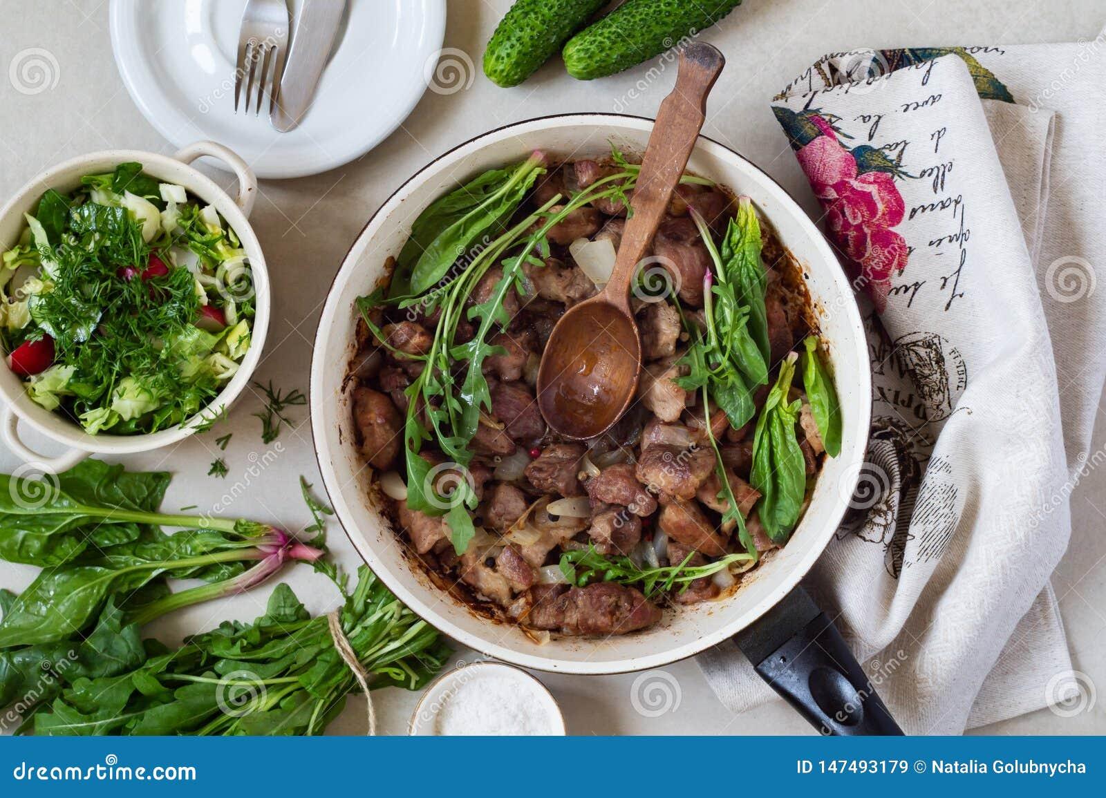 Bratpfanne des gebratenen Fleisches mit Gr?ns und Zwiebeln gulasch Nahe Sch?ssel mit Frischgem?sesalat, -Arugula und -spinat