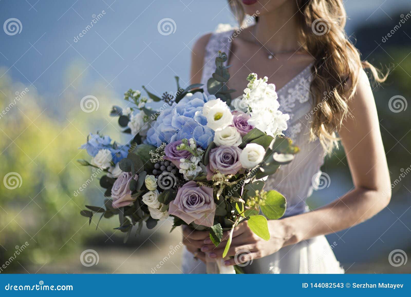 Braut hält Hochzeitsblumenstrauß auf Naturhintergrund