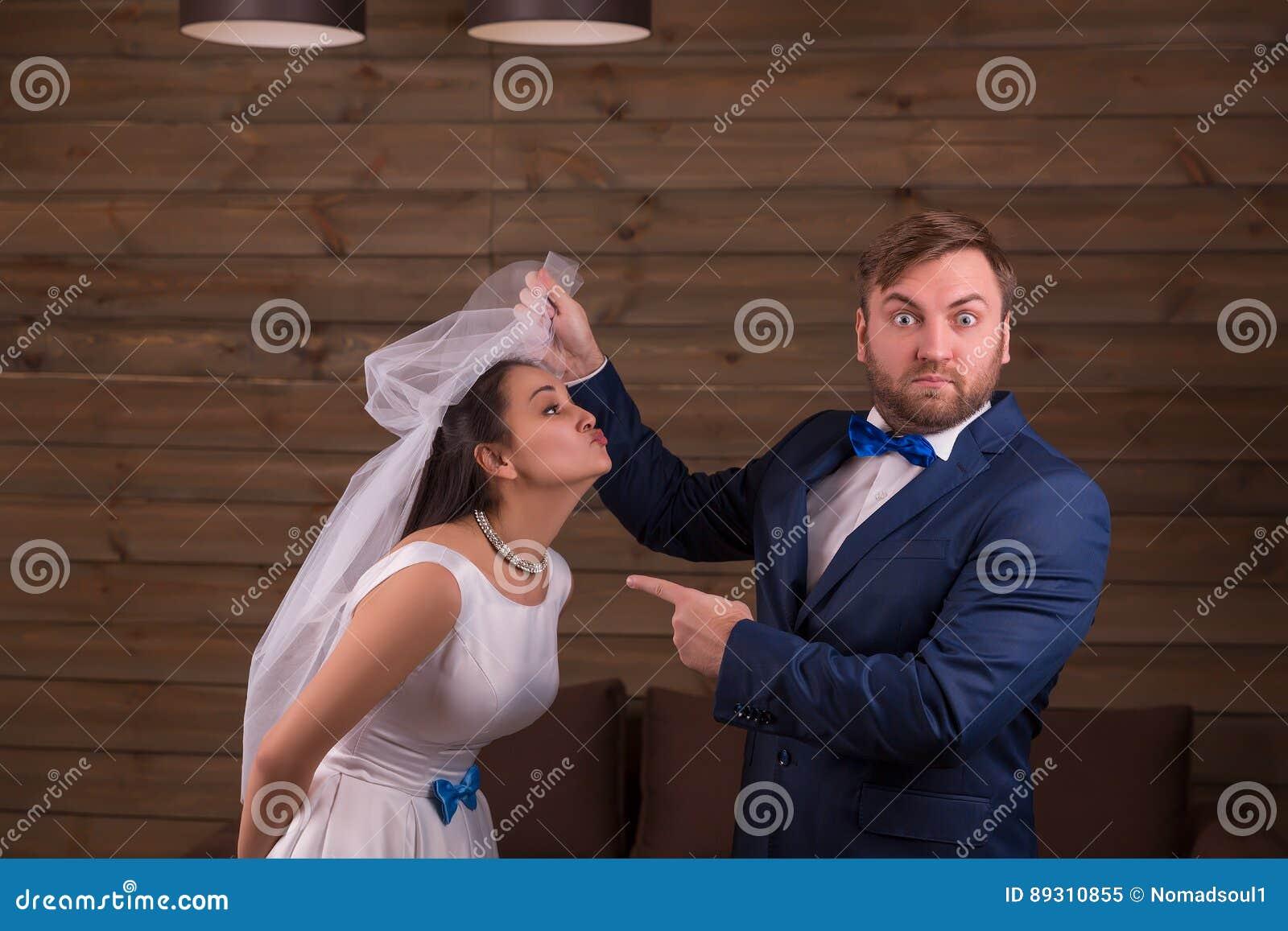 Braut im weißen Kleid gegen überraschten Bräutigam