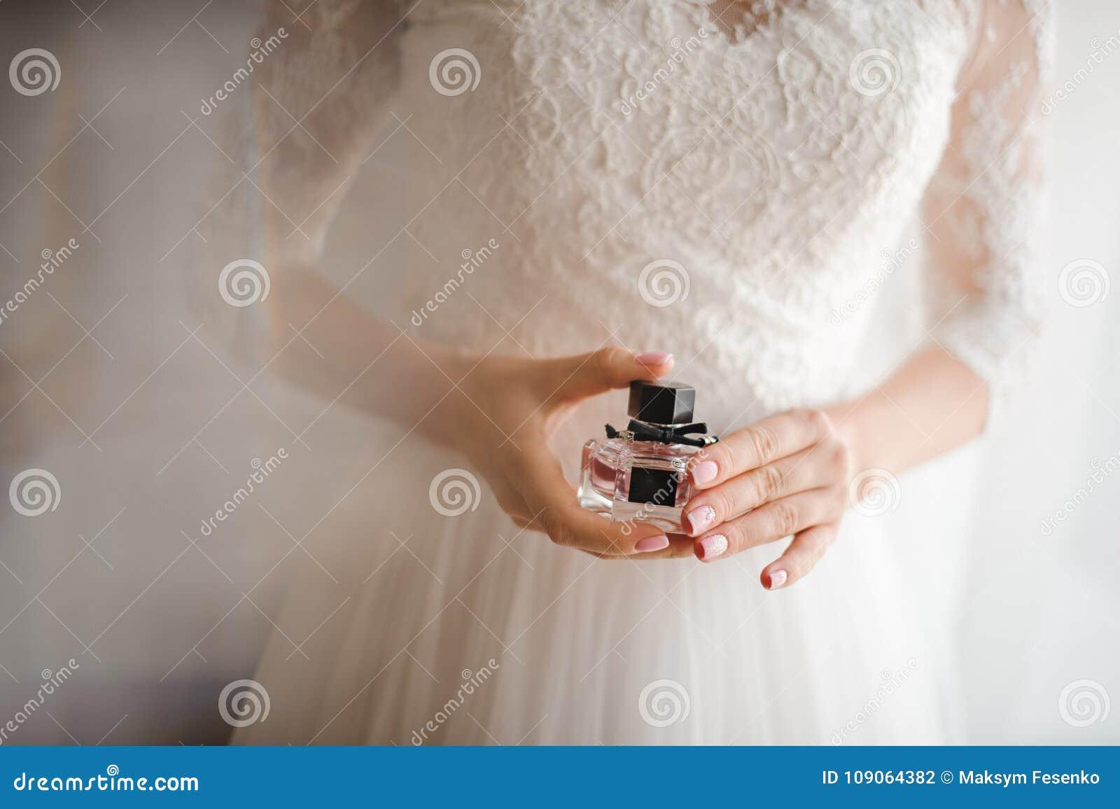 Braut mit französischer Maniküre hält eine Flasche Parfüm