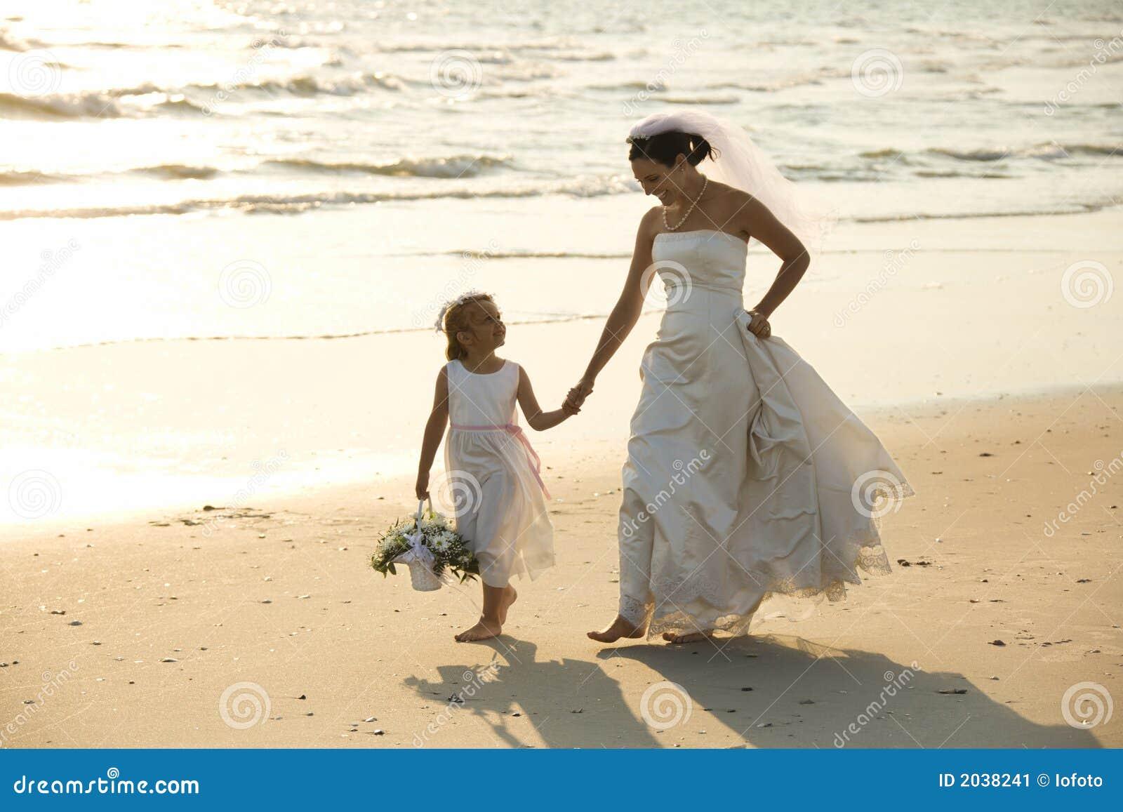 Braut- und Blumenmädchen, das auf Strand geht.