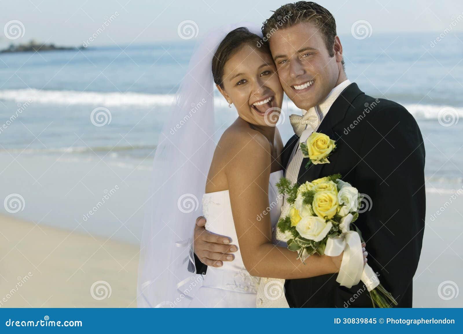 Braut und Bräutigam Embracing On Beach