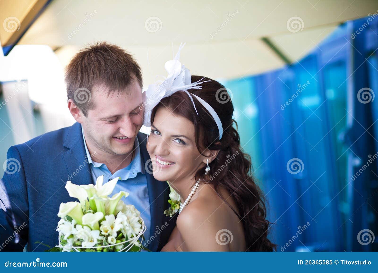 Braut und Bräutigam lacht nahe dem Glas