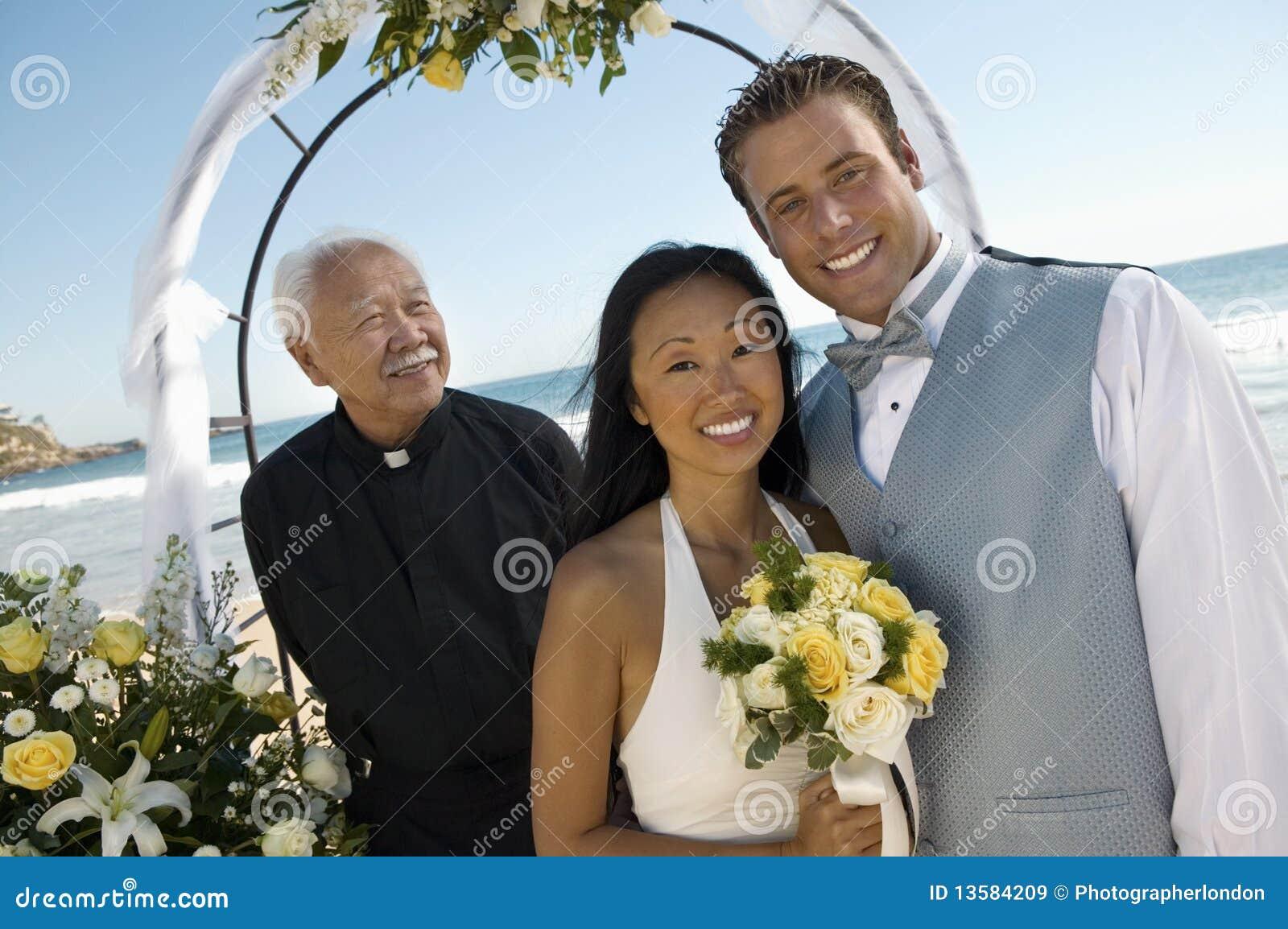 Braut und Bräutigam mit Priester unter Torbogen