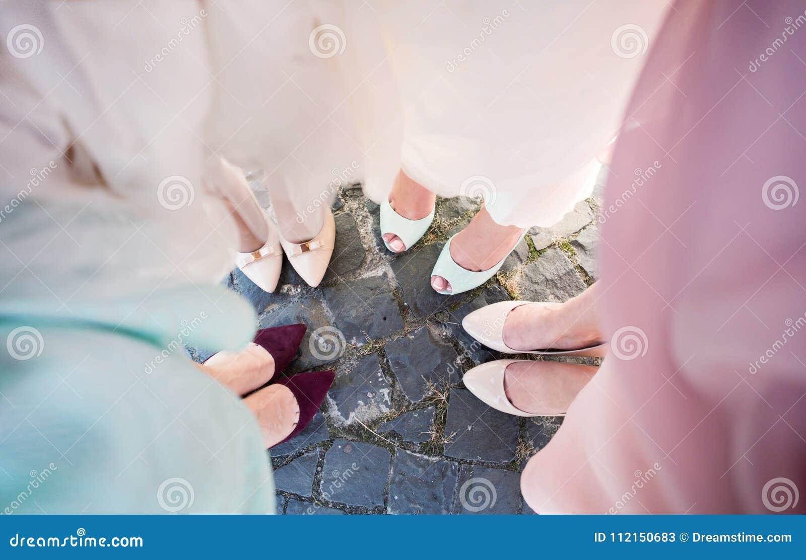 Brautjungfernbeine Braut mit ihren Freundinnen in farbigen schönen Kleidern im Hochzeitsfest