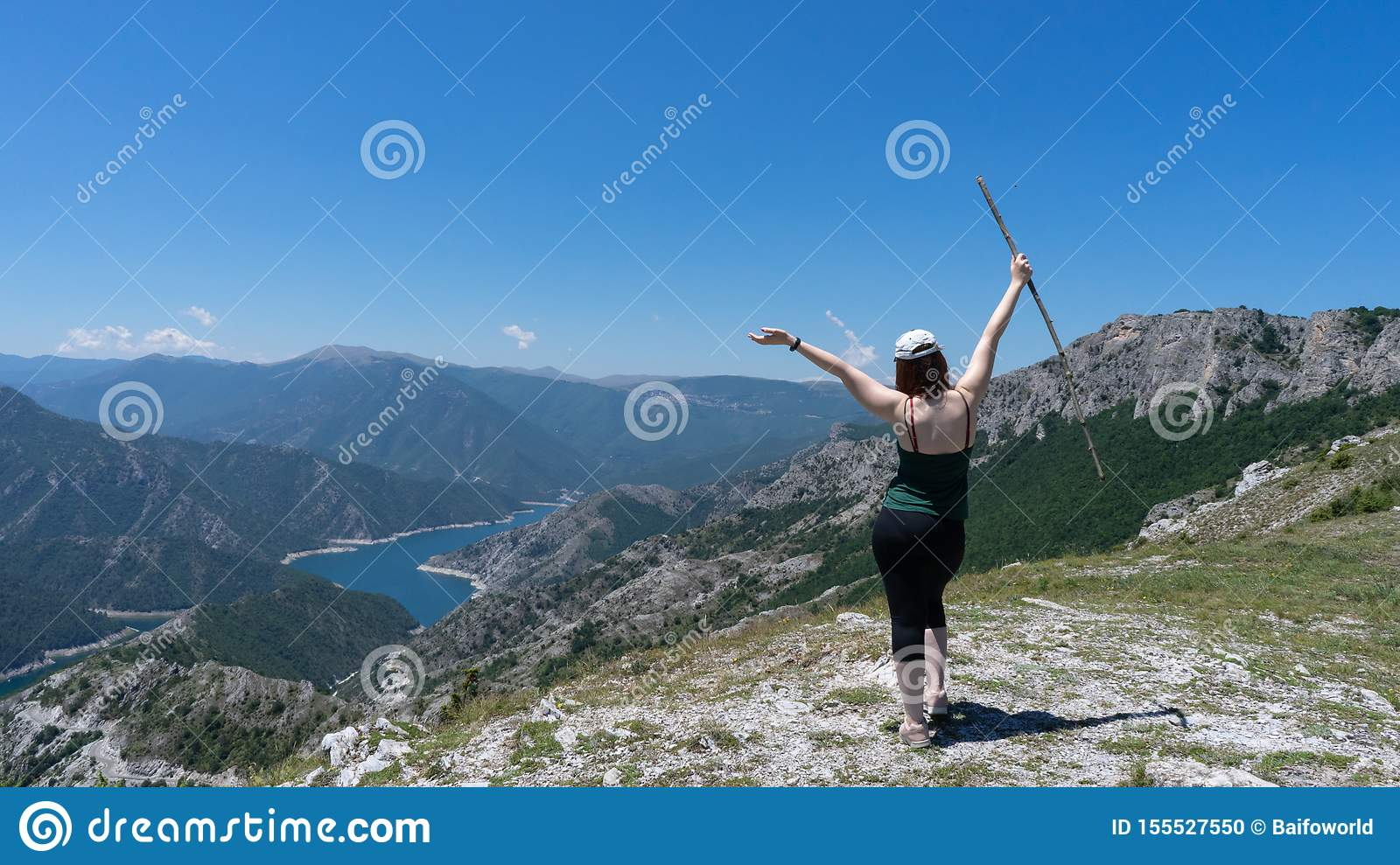 Brave girl conquering mountain peaks of mountains. Happy freedom hiker with hat and open arms Walking with wood stick, standing